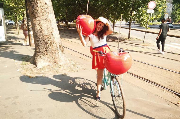 ragazza in bici con ciliegie